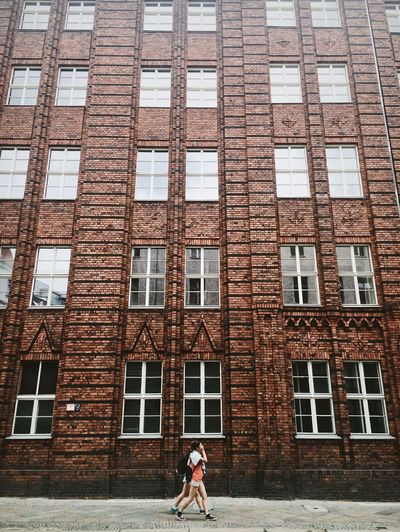 Architecture Berlin Brick Wall City Passerby Brick Building Building Exterior Built Structure Daily Life Day Old Buildings People Red Wall Streetphotography Two Women Walking Windows