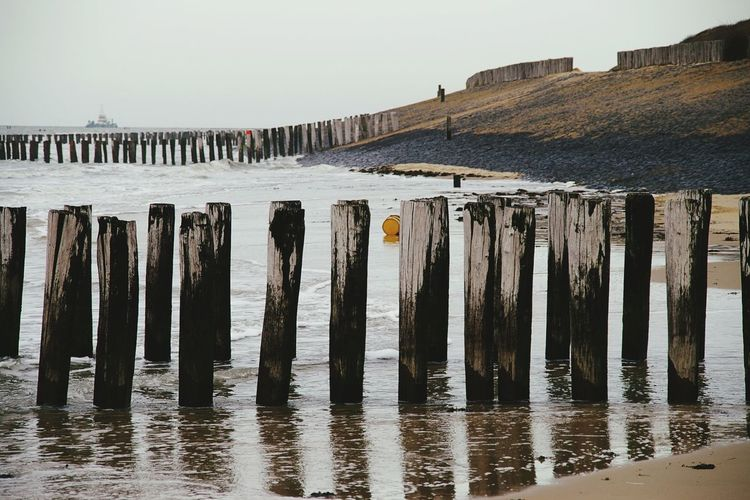 Wooden Groynes On Shore At Sea Against Sky