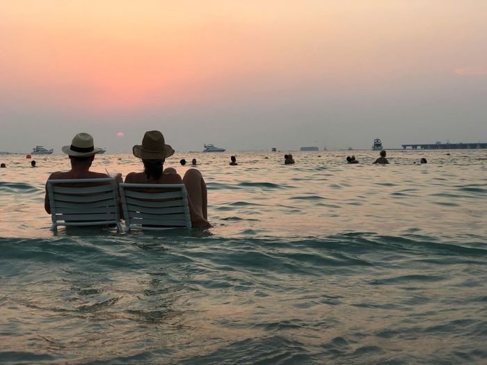 An instant between us. Water Sea Sky Sunset Beauty In Nature Beach Nature Land Scenics - Nature Horizon Over Water Real People Men Orange Color Horizon Tranquility Rear View Waterfront Idyllic Group Of People Outdoors