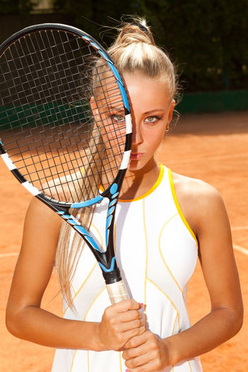 Portrait of woman holding tennis racket at court