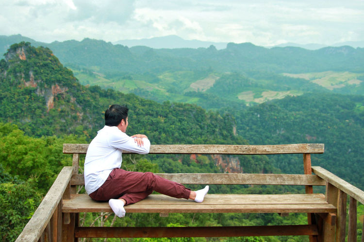 Man sitting on bench against green mountains