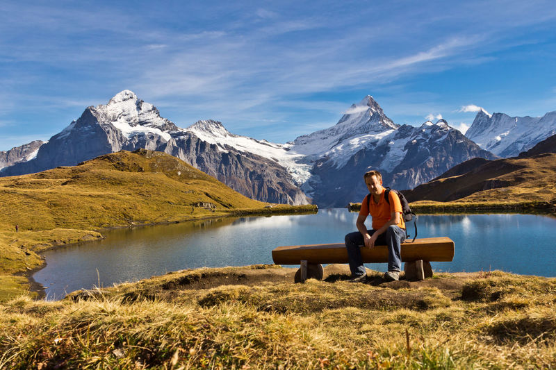 Man sitting on bench against lake with mountains and sky