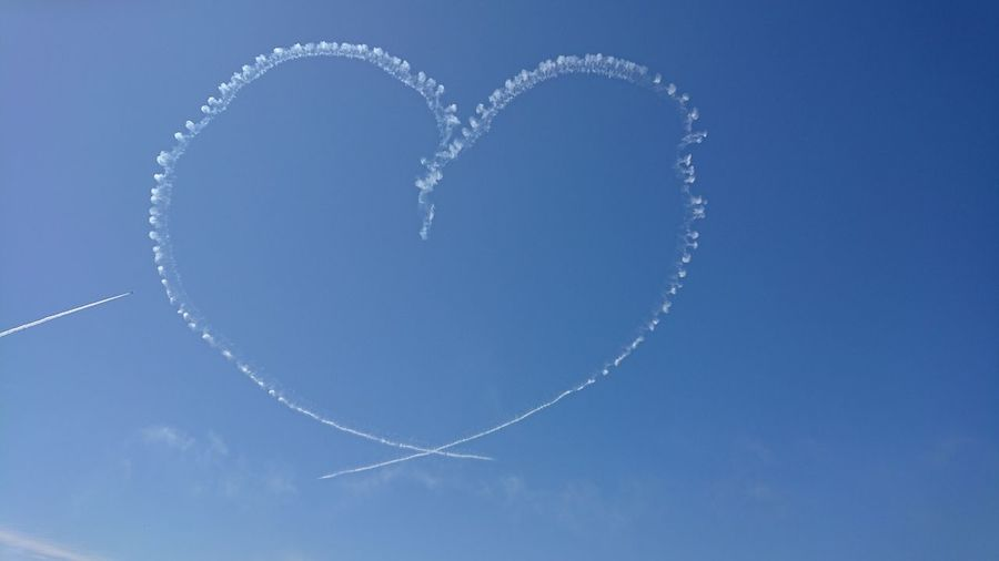 Low angle view of heart shape made from vapor trails against blue sky