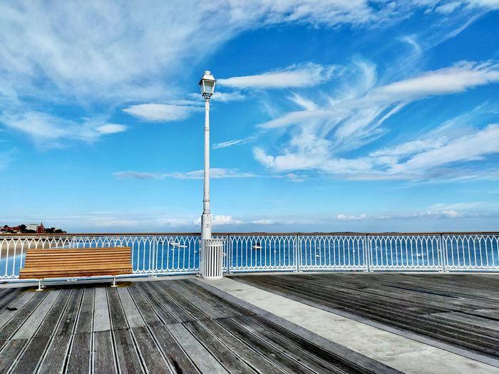 Street lights on pier by sea against blue sky
