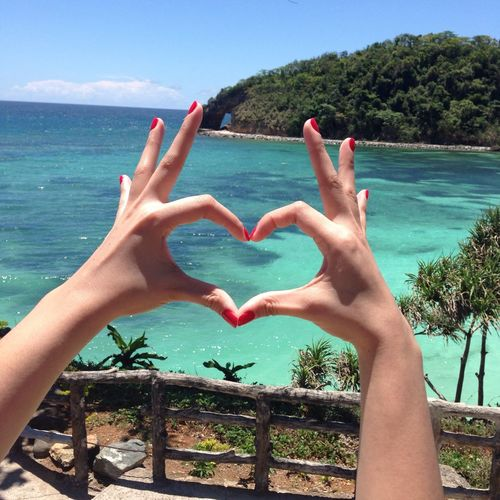 Close-up of hands forming heart shape against blue sea