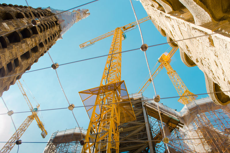 Low Angle View Of Yellow Metallic Cranes At Sagrada Familia Against Sky