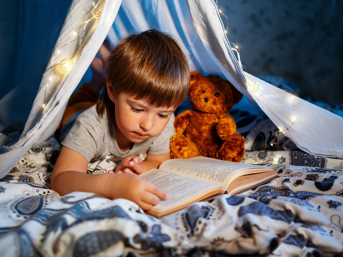 Little boy reads book with teddy bear. toddler plays in tent made of linen sheet on bed. coziness.