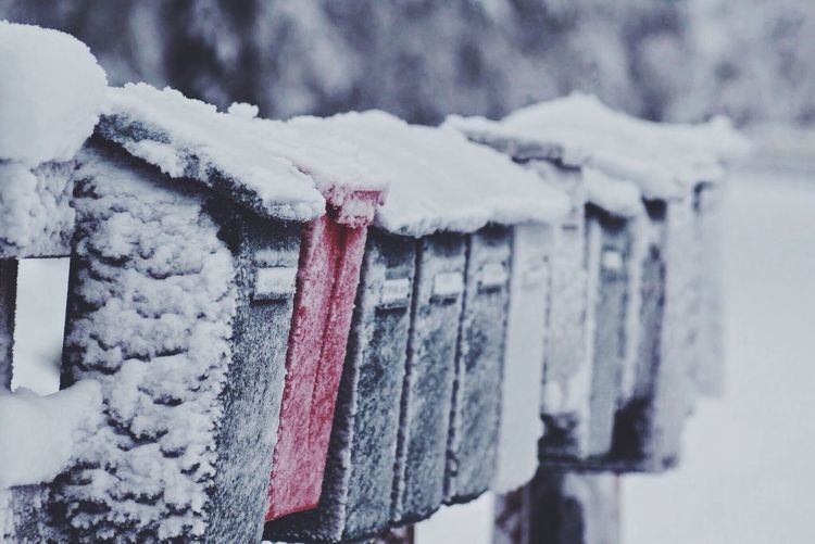 Close-up of snowed mailboxes in a row
