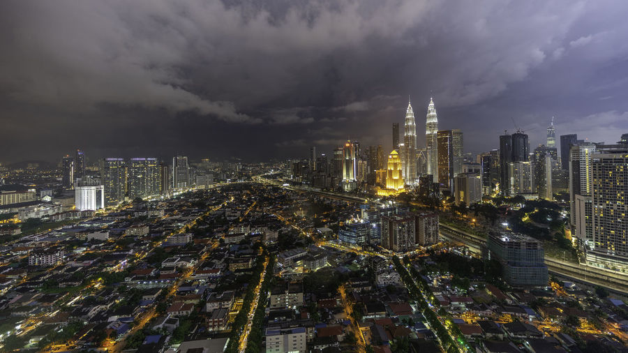 High angle view of illuminated buildings against sky in city