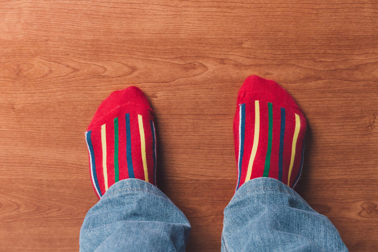 Low Section Of Person Wearing Socks On Wooden Floor