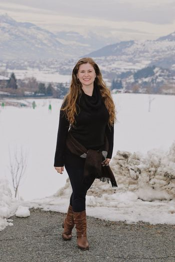 Portrait of smiling woman standing on road against snowcapped mountain