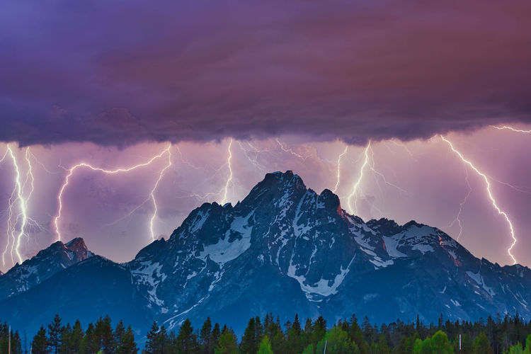 Panoramic view of lightning over mountains against sky
