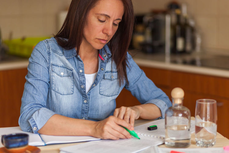 Woman analyzing budget while sitting on table at home