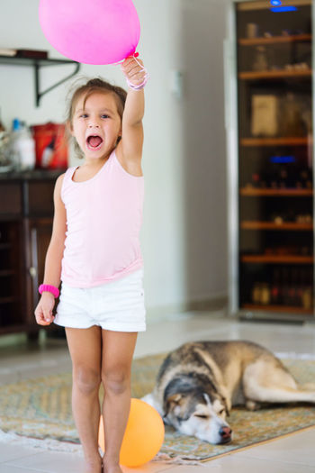 Little girl standing in the living room with a balloon and her dog sleeping on the floor