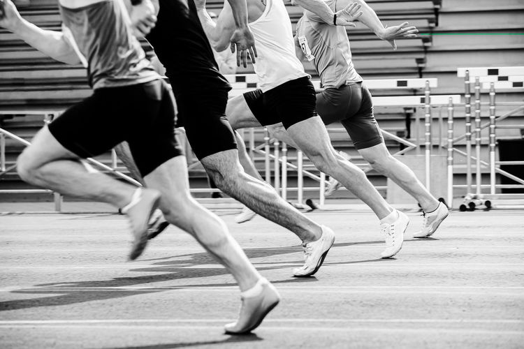 Run sprint race male athletes at stadium black and white photo