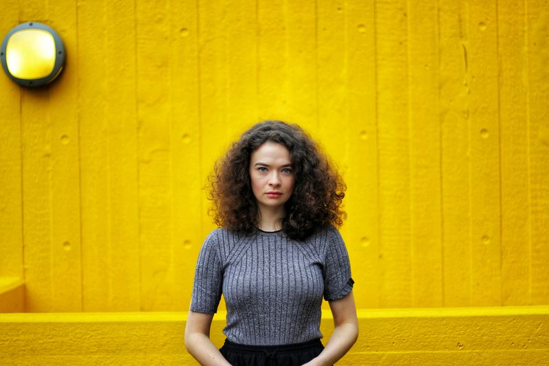 EJ Martin EyeEmNewHere EyeEm Selects Portrait Beautiful Woman Yellow Curly Hair Looking At Camera Front View Frizzy Yellow Background Posing