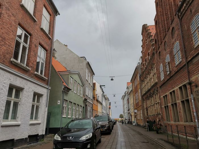 Cars on road amidst buildings against sky