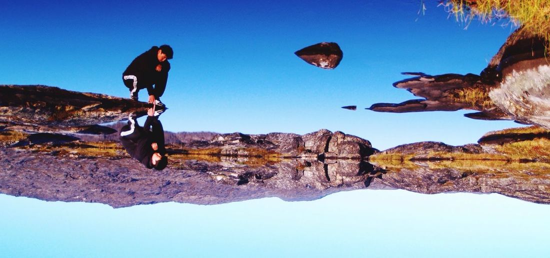 Low angle view of man standing on rock formation against clear blue sky