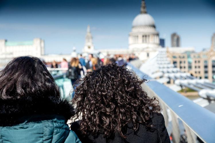 Rear view of women on london millennium footbridge against st paul cathedral