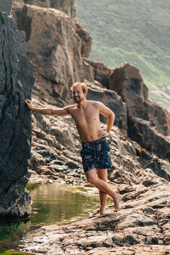 Full length of shirtless man standing on rock at beach