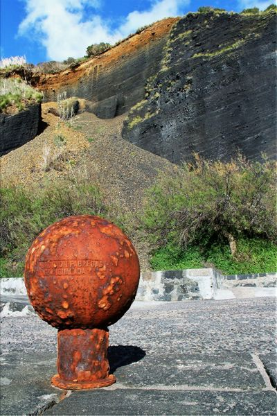 The World On A Rusty Pedestal Azores Cloud - Sky Day Faial Island Footpath Geology Horta Mooring Post Mountain No People Non-urban Scene Outdoors Physical Geography Quay Side Red Rusty Metal Sky Tourism Tranquil Scene Tranquility Travel Destinations Vacations Volcanic Island Volcanic Layers Volcanic Rock
