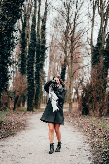 Full length of woman photographing in forest