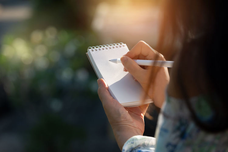 Hand writing on note pad. Woman with long hair hands holding blank note writing with white pen relaxing by the pool at sunset ,water bokeh background. Dear Mom Activity Adult Art And Craft Close-up Craft Creativity Day Drawing - Activity Focus On Foreground Hairstyle Hand Holding Leisure Activity Lifestyles Missing Someone One Person Paper Real People Selective Focus Sitting Water Bokeh Women