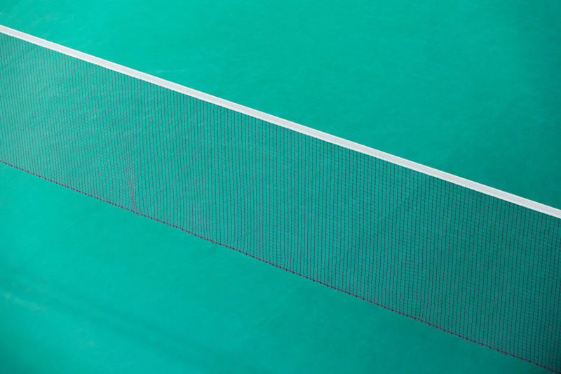 Badminton net indoor on badminton court, closeup view of badminton net with blurry background Absence Backgrounds Close-up Competition Court Day Dividing Line Empty Full Frame Green Color High Angle View Net - Sports Equipment No People Outdoors Pattern Sport Tennis Tennis Net Textured  Turquoise Colored White Color Yard Line - Sport
