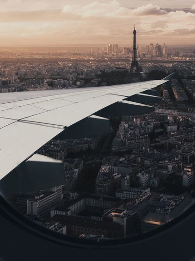 Cropped Image Of Airplane Wing Over Cityscape Seen Through Window During Sunset