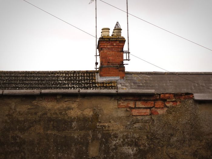 Urban Decay Deceptively Beautiful Old Buildings Brick Wall Faded Beauty Check This Out Urban Geometry Urban_collection Urban Landscape Chimneys And Aerials Rooftops Collection Wires In The Sky Showcase May Hello World
