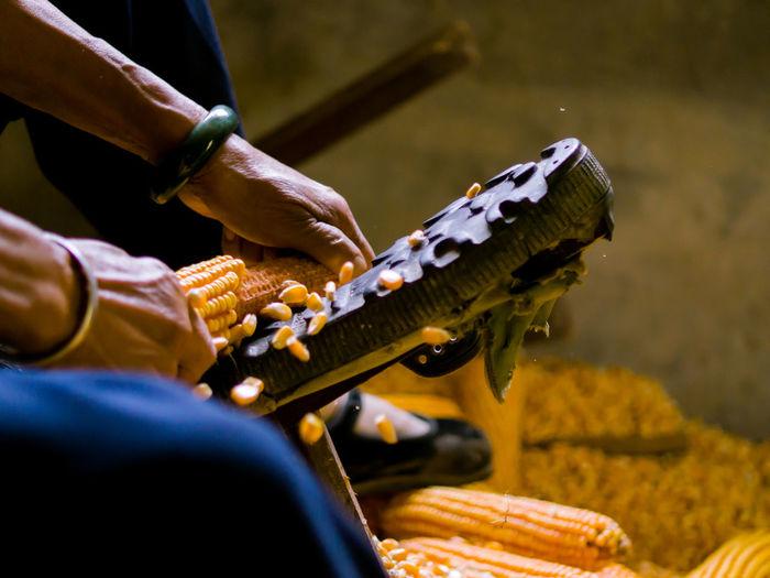Cropped hands of man removing corn kernels in workshop