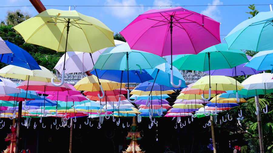 Multi colored umbrellas hanging at market stall in city