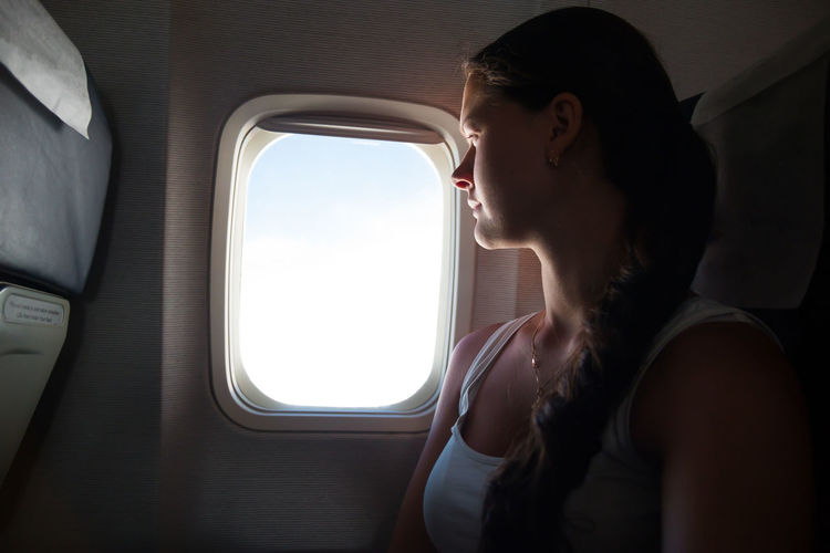 Young Woman Looking Through Window While Sitting In Airplane