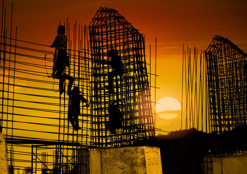 silhouette construction team working on high ground Construction Site Gold Man Planning Worker Architecture Building Building Exterior Built Structure Concrete Construction Site Day Engineer High Section Labor Low Angle View One Person Orange Color Outdoors Safety Silhouette Steel Strategic Sunset Team