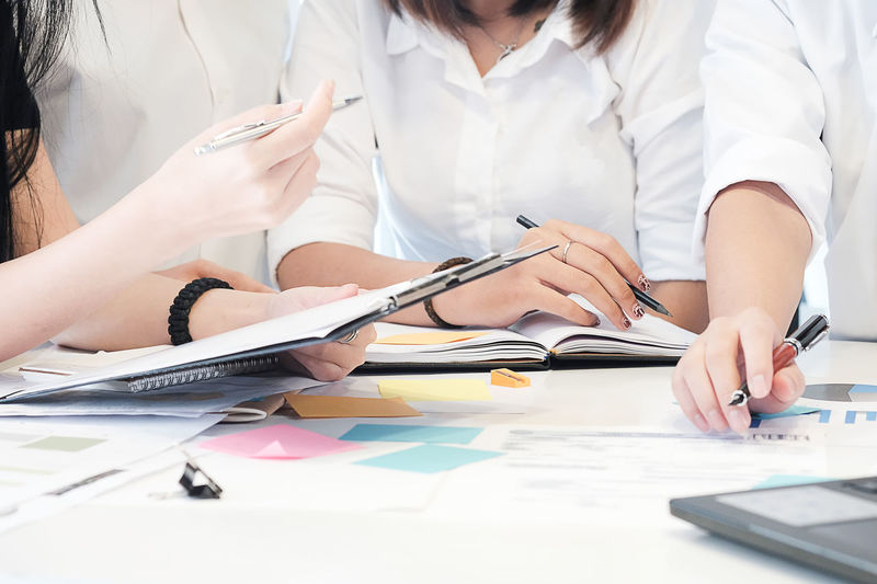 Business people Consulting and business planning. Adult Business Desk Document Front View Furniture Holding Indoors  Midsection Occupation Paper Paperwork Pen People Professional Occupation Real People Sitting Table Women Working Writing
