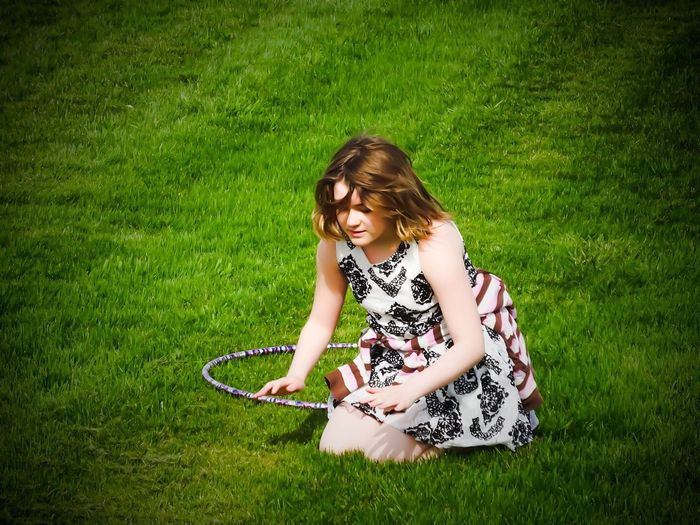 High angle view of girl kneeling by plastic hoop on grassy field