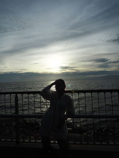 Woman standing by railing against sea during sunset