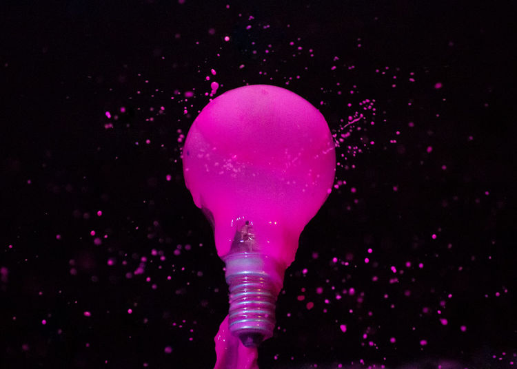 Close-up of electric bulb with pink liquid against black background