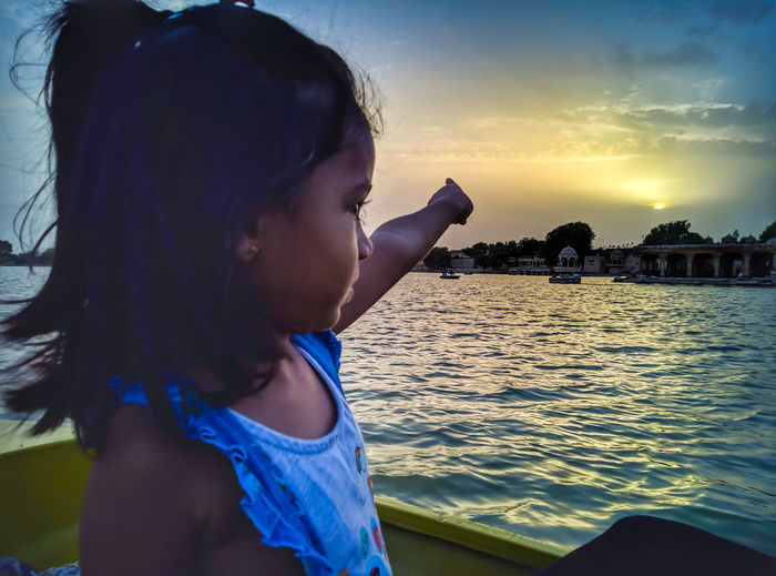 Girl Pointing While Looking At Sea Against Sky During Sunset