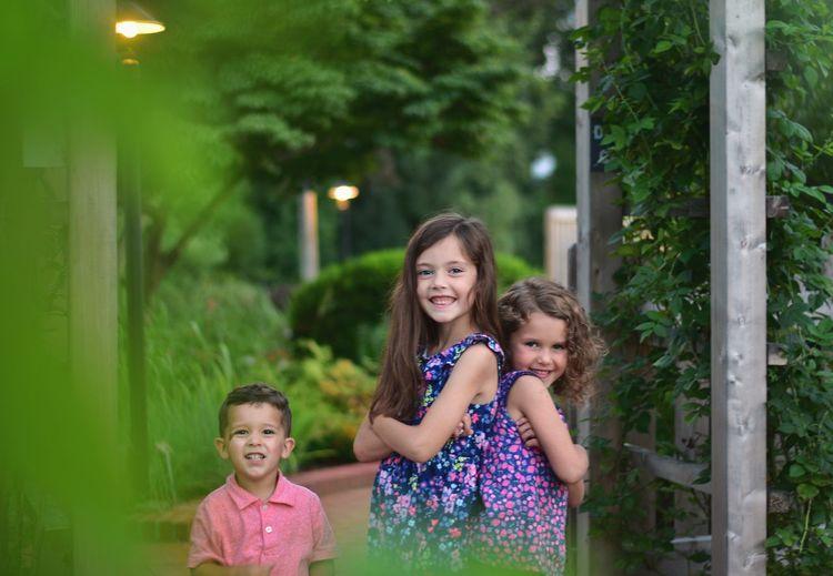 Portrait of happy siblings standing in park