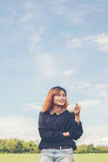 Smiling young woman with coffee cup standing against sky
