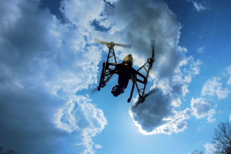 Low angle view of drone flying against cloudy sky