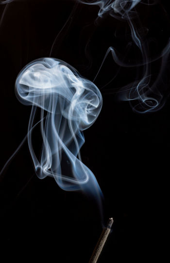 Close-Up Of Smoke Over Incense Against Black Background