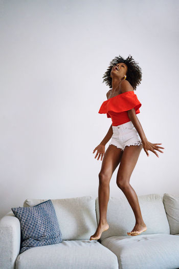 Full length of woman standing on sofa at home