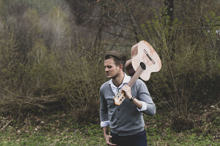 Young man with guitar standing in forest