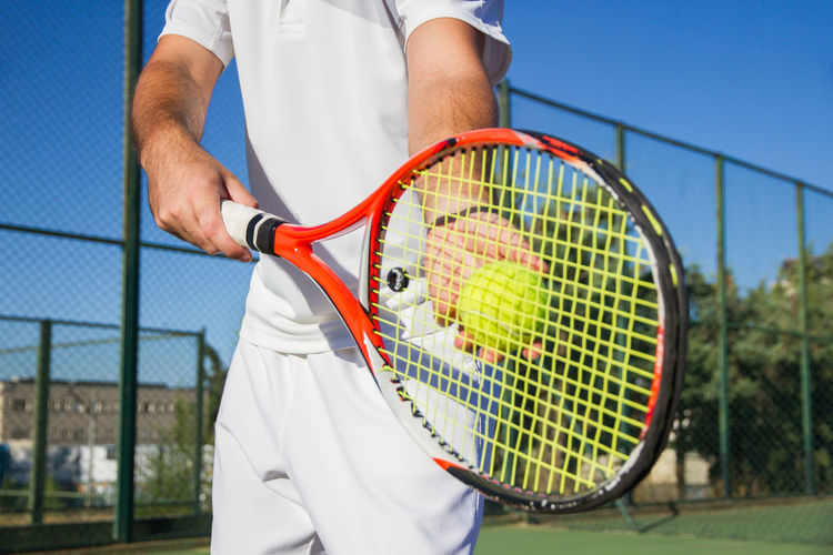 Midsection Of Man Playing Tennis Against Blue Sky In Court