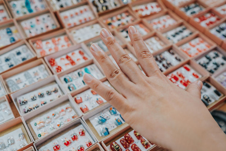 Cropped image of woman choosing artificial fingernails in store