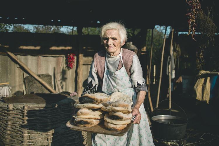 Senior woman holding food outdoors