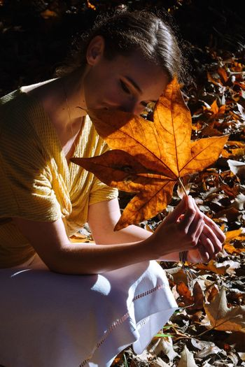 Woman sitting on maple leaves during autumn