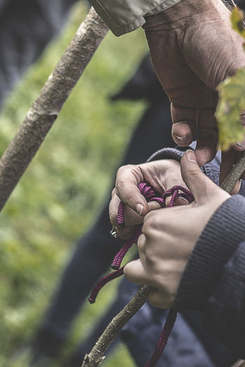 Cropped Image Of Teacher Teaching Student To Tie Knot